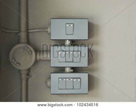 Three Switch Of Lighting Mounted On Wall.