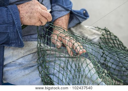Hands of commercial fisherman mending nets