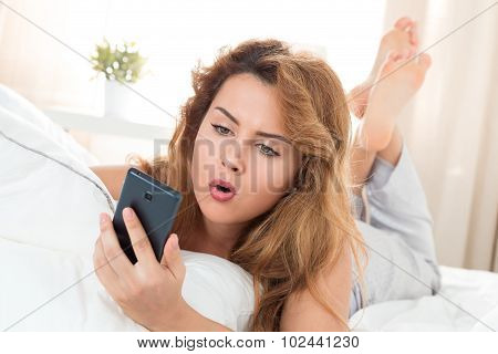 Young Beautiful Woman Laying In Her Bed And Looking At Mobile Phone
