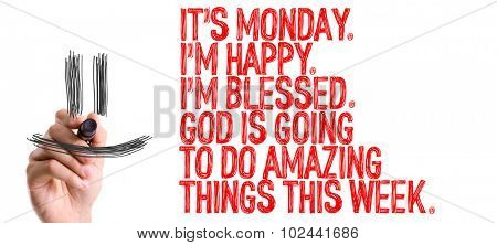 Hand with marker writing: Its Monday Im Happy Im Blessed God Is Going to do Amazing Things This Week