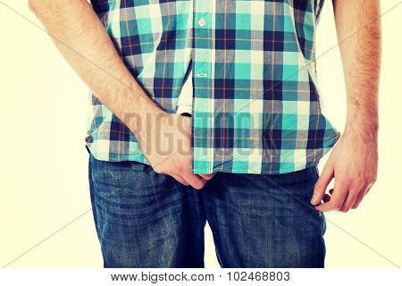 Young man holding his crotch because of pain.