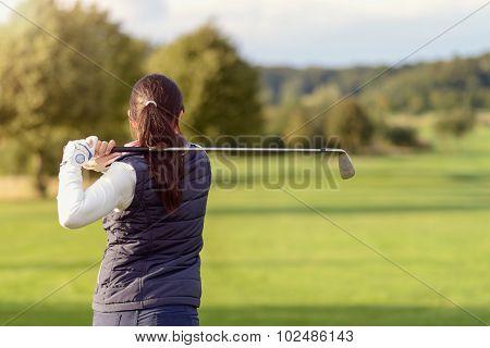 Female Golfer Striking The Golf Ball