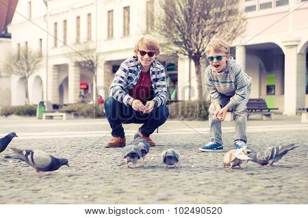 Two Brothers Feed A Doves On The Old City Square