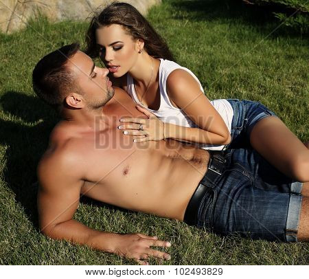 fashion outdoor photo of sensual impassioned couple.beautiful gorgeous woman and tanned handsome man embracing in summer garden poster