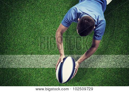 Rugby player lying in front with ball against pitch with line