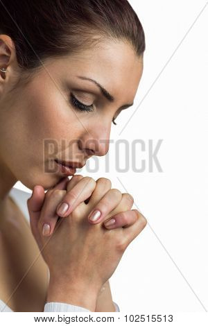 Close-up of woman praying with joining hands and eyes closed against white background