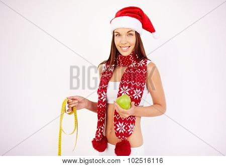 Fit young woman in Santa cap, scarf and activewear holding green apple and measuring tape