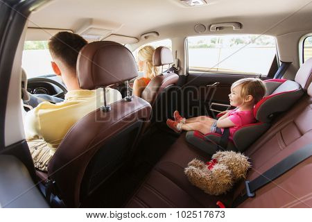 family, transport, safety, road trip and people concept - happy parents with little child driving in car