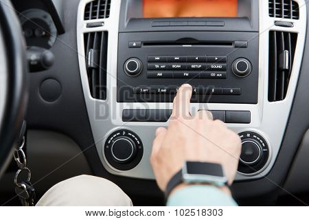 transport, road trip, car driving, technology and people concept - close up of male hand turning on radio on control panel system in car poster