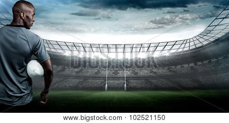 Rear view of sportsman with rugby ball against rugby stadium