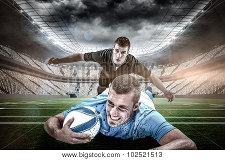Confident rugby player lying in front with ball against rugby stadium