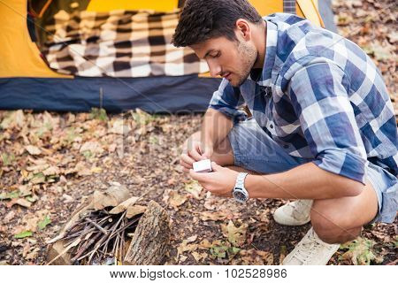 Portrait of a young man kindle bonfire in the forest