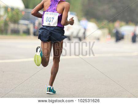 Marathon runner running on city road