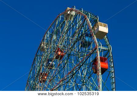 Wonder Wheel in Coney Island against blue cloudless sky. poster