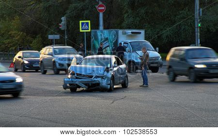 Car Accident. Destroyed Audi In Middle Of The Intersection And Frustrated Driver With Phone