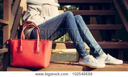 Girl sitting on the stairs with a big red super fashionable handbags in a sweater jeans and sneakers