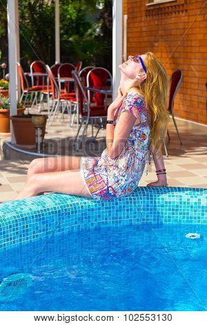 Beautiful young woman sitting near the pool