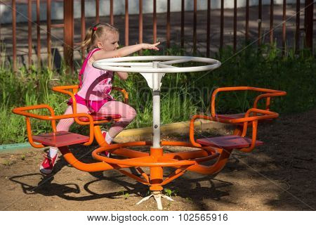 Little Girl With Pigtails Spinning On Carousel