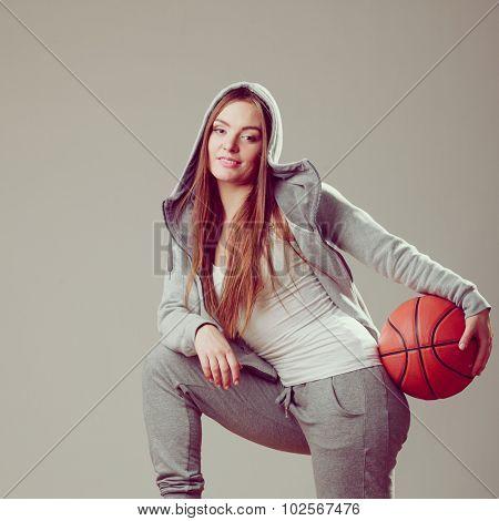 Sporty teenager girl wearing hooded sweatshirt holding basketball. Teen sport. poster