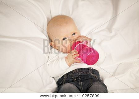 baby girl drinking from baby bottle