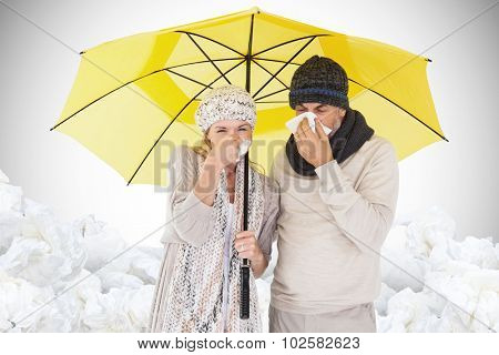 Couple sneezing in tissue while standing under umbrella against white background with vignette