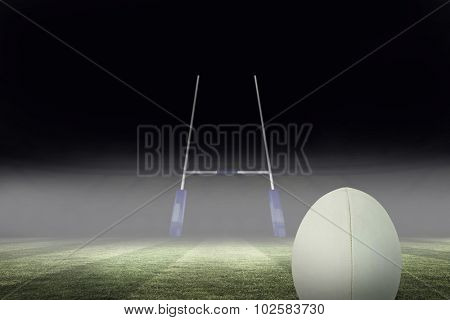 Close-up of rugby ball against rugby pitch