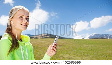 sport, people, fitness, technology and lifestyle concept - woman with smartphone and earphones doing sports and listening to music over natural background poster