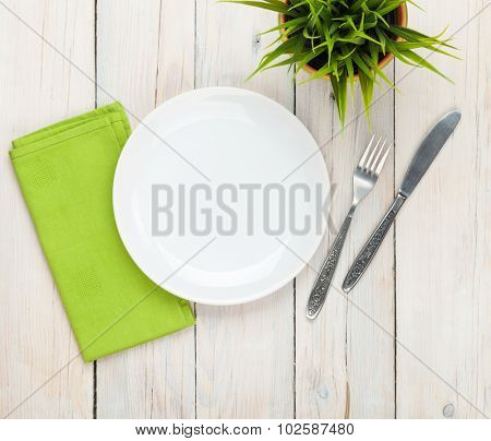 Empty plate and silverware over white wooden table background. View from above with copy space