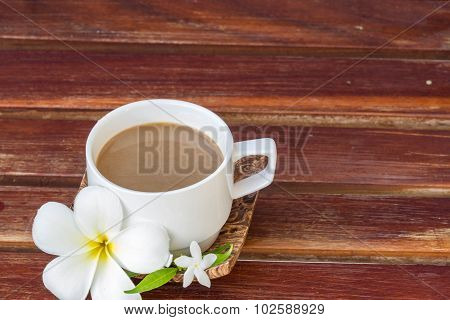Plumeria flower on wood and glass coffee