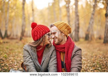 Cheerful boyfriend and girlfriend looking at one another while relaxing outdoors poster