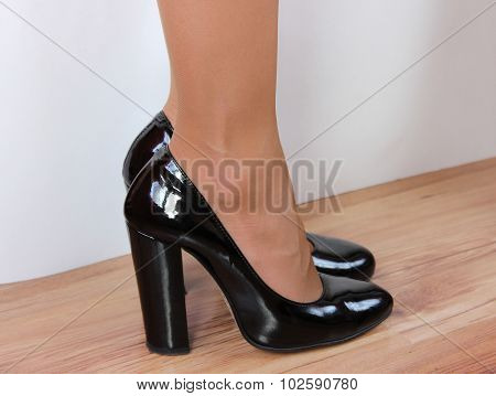 Female feet shod in black shoes with heels on a white background standing on the floor