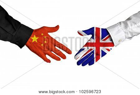 China and United Kingdom leaders shaking hands on a deal agreement