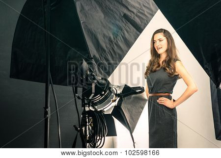 Young female model at photo shooting in modern Studio poster