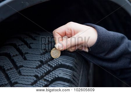 a young woman measures the tread depth of your car tire. the correct depth in the tread of a tire can prevent accidents.
