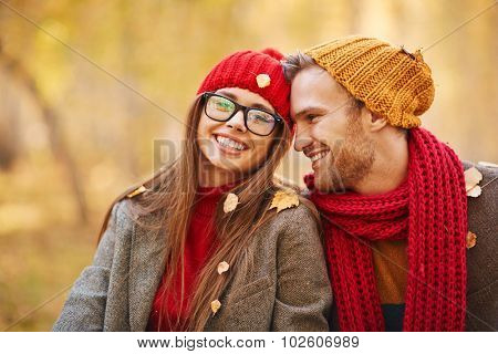 Happy young couple looking at camera during leaf fall