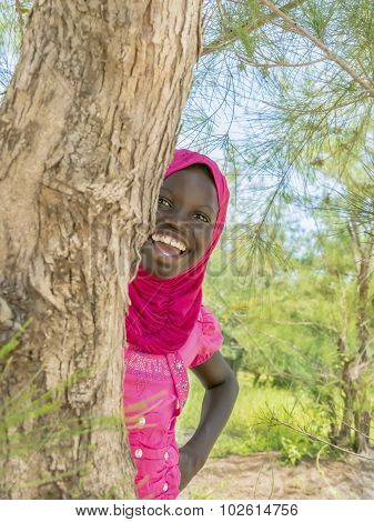 Afro girl playing hide-and-seek behind a filao tree, ten years old