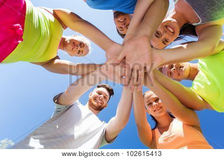 fitness, sport, friendship and healthy lifestyle concept - group of happy teenage friends with hands on top outdoors