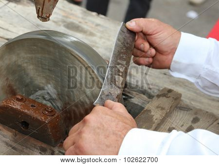 Elder While Sharpening The Blade Of The Knife On The Large Water Wheel