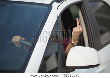 Beautiful lady showing middle finger from her car