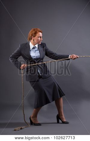 Businesswoman hauling at a rope