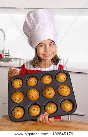 proud female child 4 or 5 years old presenting her self made muffin cakes learning baking wearing red apron and cook hat smiling happy in bakery and cooking education concept poster