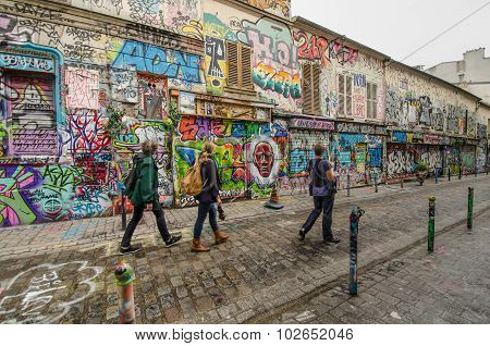 People pass by dazzling street art on Rue Denoyez in Paris