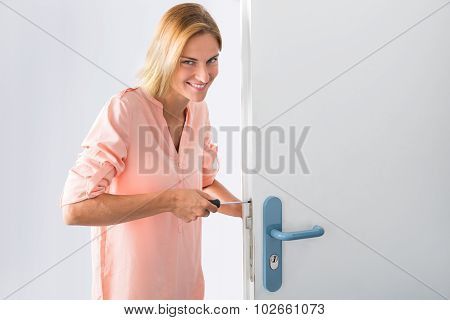 Portrait Of Young Woman Fixing Door With Screwdriver poster