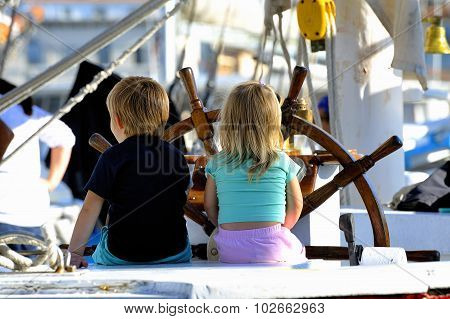 Two Young Children On The Stand Of An Old Wooden Sailing