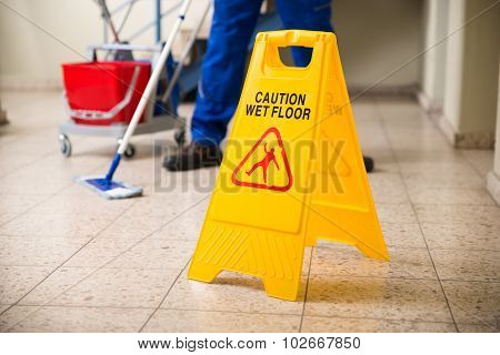 Worker Mopping Floor With Wet Floor Caution Sign