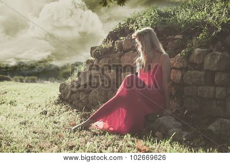 fairy like young woman in red dress and wreath of flowers in hair sit by old wall in nature, full body shot, side view