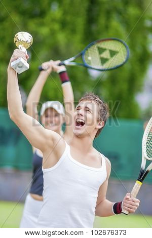 Tennis Sport Concepts: Happy Exclaiming Tennis Couple With Trophy Cup Won On Competition