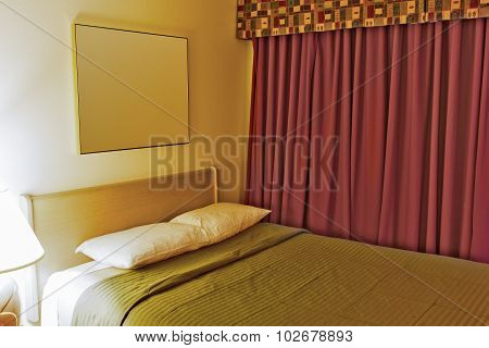 Contemporary Hotel Bedroom With One King Size Bed Arranged In Pastel Colors And Red Curtains