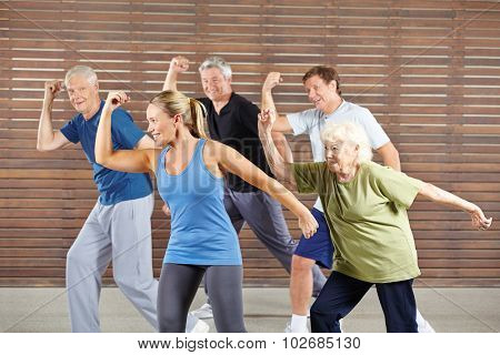 Happy senior people learning dancing in gym class
