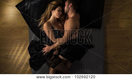 Passionate couple is cuddling after making love poster